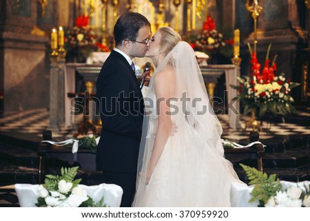 Newlywed bride and groom first kiss at wedding ceremony in church - stock photo