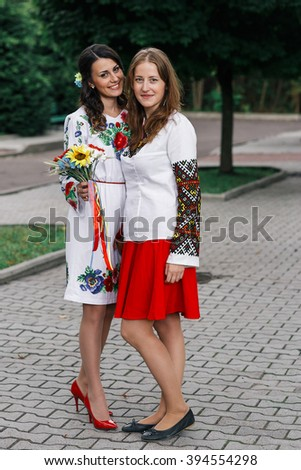 Newlywed bride & bridesmaid in traditional ukrainian clothes posing outdoors