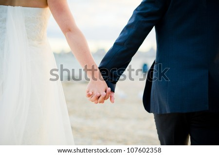 Newlywed couple holding hands - stock photo