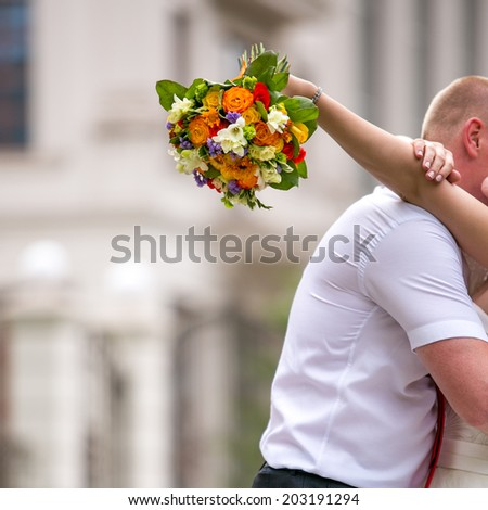 Newlywed couple kisses in the street, bride holding wedding flowers. focus on flowers in a hand - stock photo