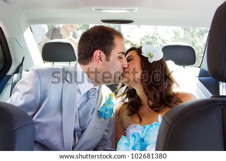 Newlywed couple kissing each other in limousine - stock photo