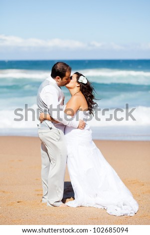 newlywed couple kissing on beach