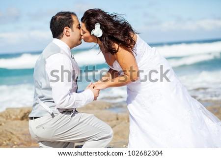 newlywed couple kissing on beach rocks - stock photo