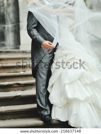Newlywed couple kissing on the street  - stock photo