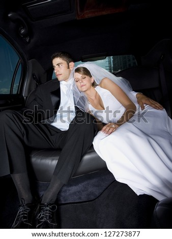 Newlywed couple sitting in a car