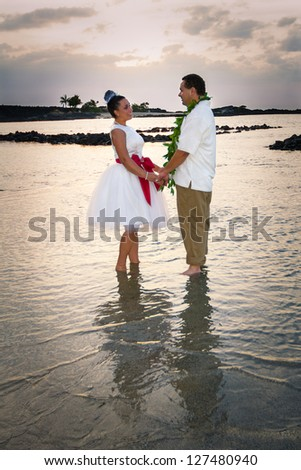 Newlywed couple standing in the warm, shallow waters of Hawaii. Vertical portrait. - stock photo