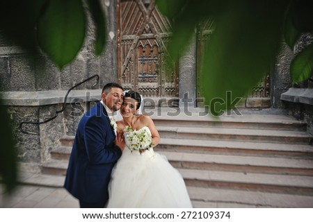 newlywed embrace near of stairs old church - stock photo