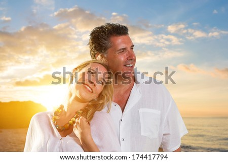 Newlywed happy young couple embracing enjoying ocean sunset during travel holidays vacation getaway.