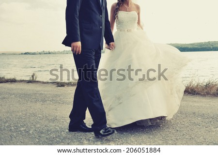 Newlywed young caucasian couple walking by the riverside. - stock photo