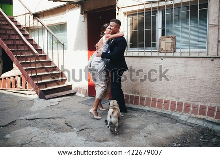 Newlyweds and dog in the courtyard