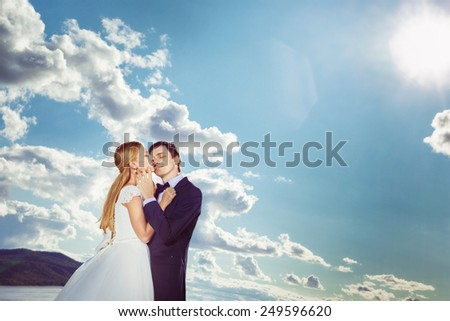 Newlyweds are kissing outdoors ar bright summer sky background.