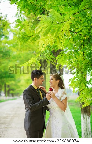 Newlyweds at park looking each other, broom is giving to her a flower. Bride, broom, bright photo. - stock photo
