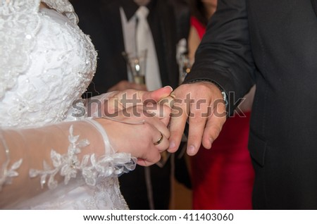 Newlyweds. Bride puts a wedding ring on groom. Hands of newlyweds and wedding rings. Commitment, happiness and love. - stock photo