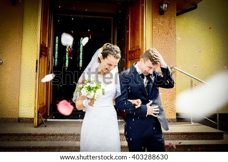 Newlyweds coming out of the church after wedding ceremony. Their are standing in front of stairs under the rain of rose petals. Sunny Wedding Day. - stock photo