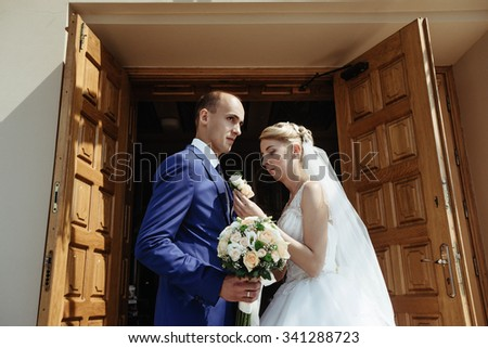 newlyweds elegant handsome groom and beautiful stylish happy blonde bride after wedding ceremony throwing candies on the background of old church