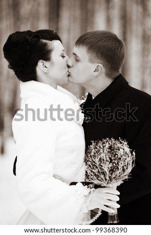 Newlyweds embraces outdoors in the forest in winter - stock photo