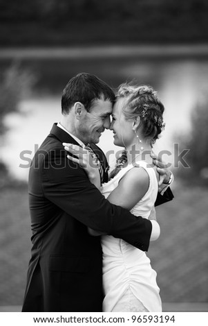 Newlyweds embraces outdoors. River on the background. Black and white