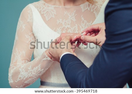 Newlyweds exchange rings, groom puts the ring on the bride's hand in marriage registry office - stock photo