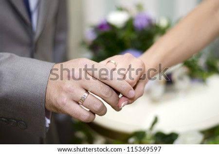 Newlyweds - hand in hand with wedding rings on a background of flowers.