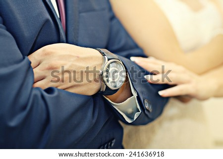 newlyweds hands during wedding watch concept - stock photo