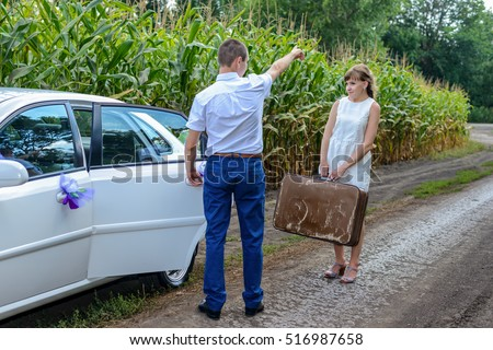 Newlyweds having their first argument with the young woman leaving the bridal car with her suitcase and walking off down a farm road with her suitcase as her husband waves goodbye behind her