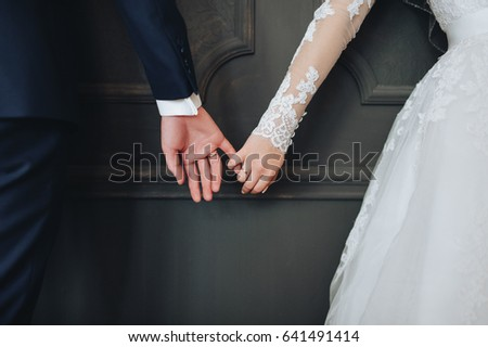 Newlyweds hold hands. Bride and groom.