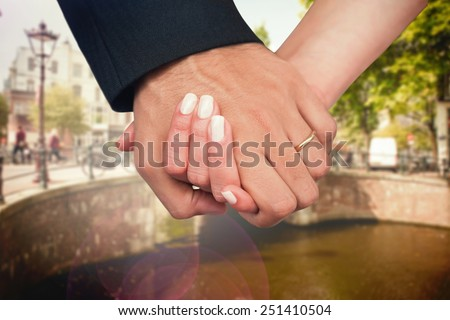 Newlyweds holding hands close up against bridge in amsterdam