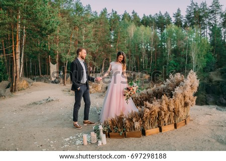 Newlyweds holding hands, laugh and smile, happy and joyful moment. Groom is looking on his beautiful bride. Outdoors wedding ceremony