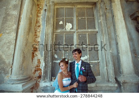 newlyweds hugging and smiling background old castle