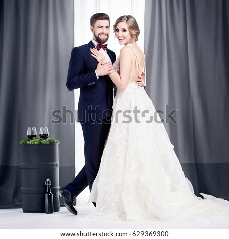 Newlyweds in a wedding dress and a suit stand in a ballroom