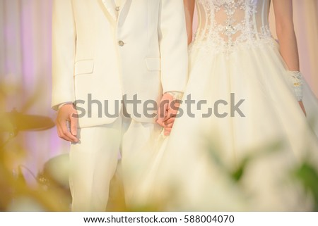 Newlyweds in a white dress standing hand in hand.
