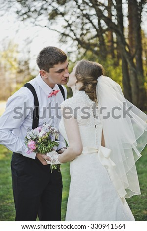 Newlyweds kissing on the background of the forest.