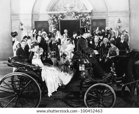 Newlyweds leaving wedding in carriage