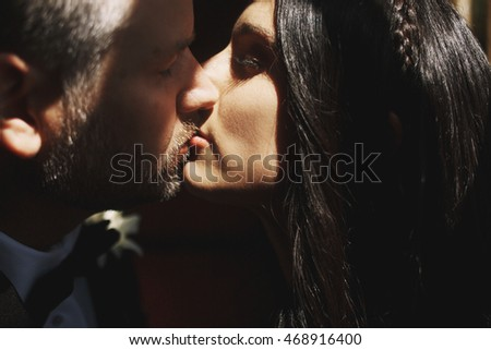 Newlyweds' lips touch each other tender while they stand in the ray of sun