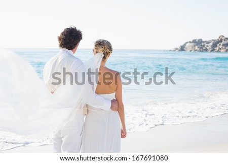 Newlyweds looking out to the sea together at the beach