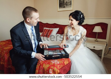 newlyweds open suitcase with money