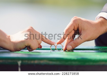 newlyweds playing with rings on bench - stock photo