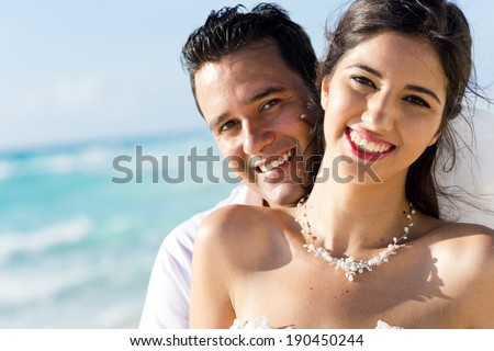Newlyweds sharing a romantic and fun moment at the beach - stock photo