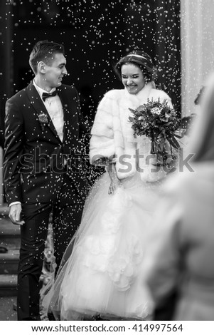 Newlyweds smile in the rain of rice  in the front of the church