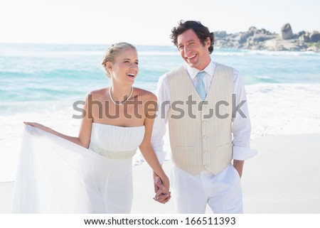 Newlyweds walking hand in hand and laughing at the beach