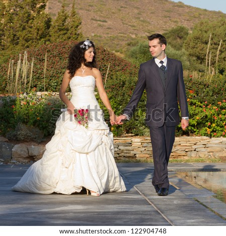 Newlyweds walking near the pool at some resort at sunset