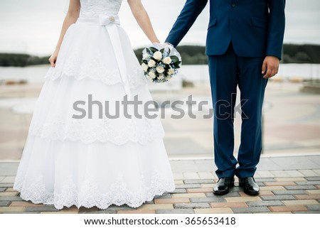 Newlyweds with a bouquet - stock photo