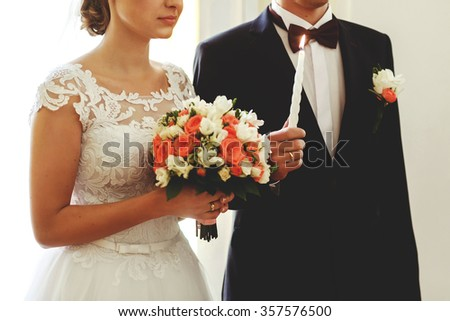 Newlyweds with bouquet of flowers and candle in hands on their wedding day - stock photo