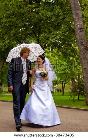 newlyweds with umbrella walk in park