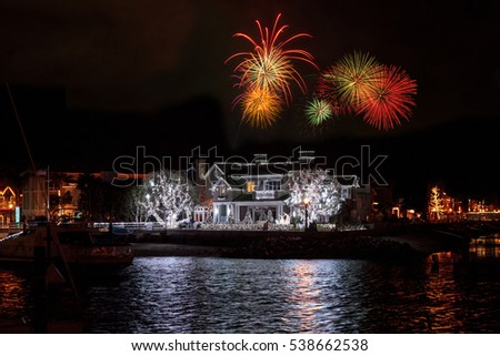 Newport Beach, CA, USA -December 16, 2016: Fireworks over holiday lights on a home and on sailboats and ships in the Balboa Harbor for the Newport Beach Christmas Boat Parade. Editorial use only.