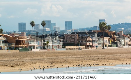 Newport Beach California 3. The coastline of Newport Beach, California on a hazy sunny morning with the Irvine city skyline in the distance. - stock photo