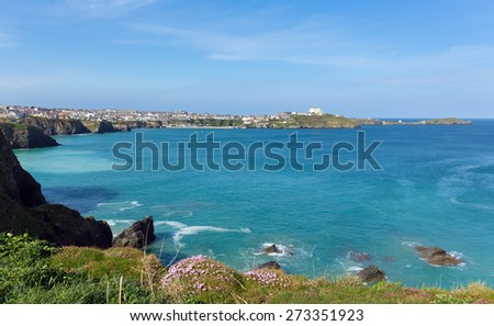 Newquay coast North Cornwall UK beautiful Cornish coast in spring with blue sky and sea and pink flowers