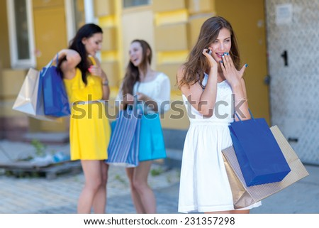 News about shopping sales on mobile phone. Young and pretty girl is talking on the sell phone and holding a shopping bags. Her friends girls are standing on the background with shopping bags. - stock photo