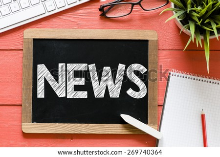 News word Handwritten on blackboard. News word Handwritten with chalk on blackboard, keyboard,notebook,glasses and green plant on wooden background - stock photo