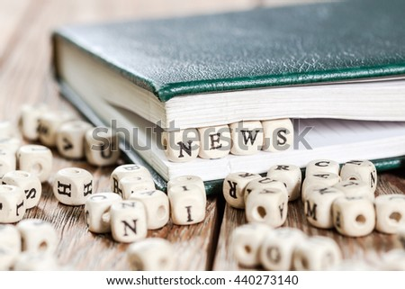News word written on a wooden block in a book. On old wooden table.
